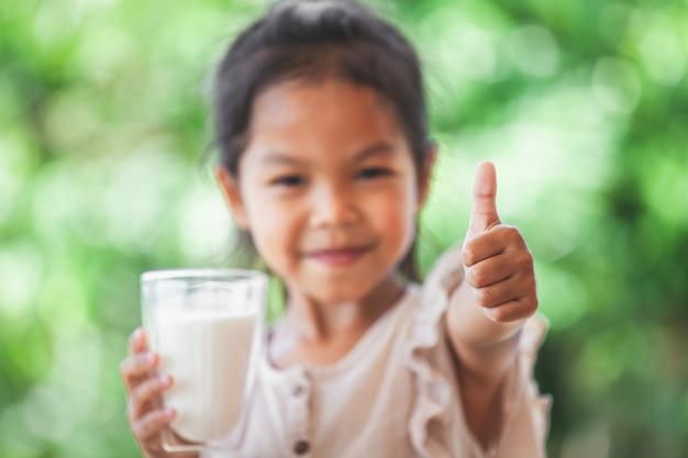Menina asiática bonito da criança que guarda o vidro do leite e faz o gesto forte