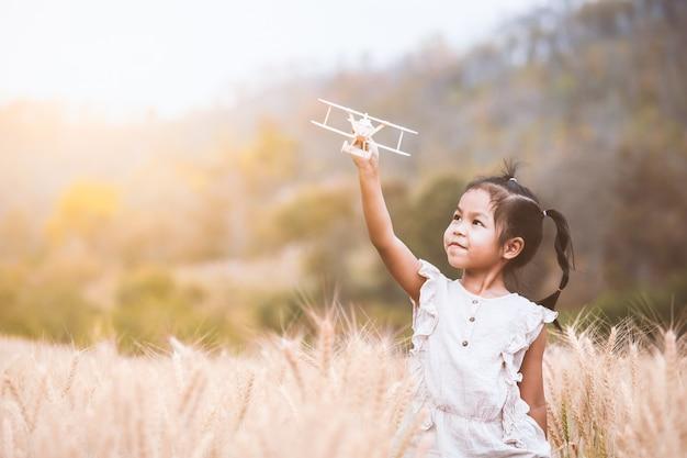 Menina asiática bonito da criança que joga com o avião de madeira do brinquedo no campo da cevada no tempo do por do sol