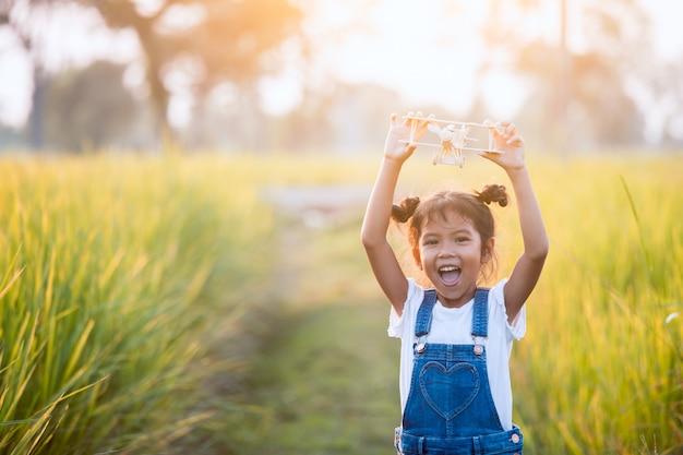 Menina asiática bonito da criança que joga com o avião de madeira do brinquedo no campo no tempo do por do sol