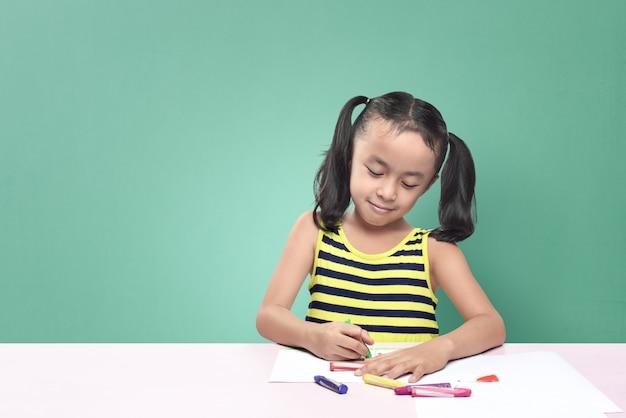 Menina asiática bonito desenho com giz de cera enquanto está sentado na mesa