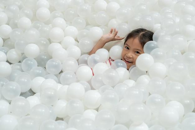 Menina asiática bonito feliz da criança que tem o divertimento a jogar com as bolas plásticas brancas no campo de jogos