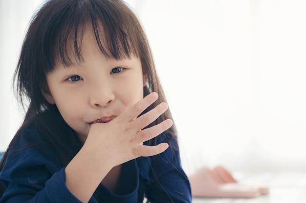 Menina asiática bonito girll chupando o dedo o polegar