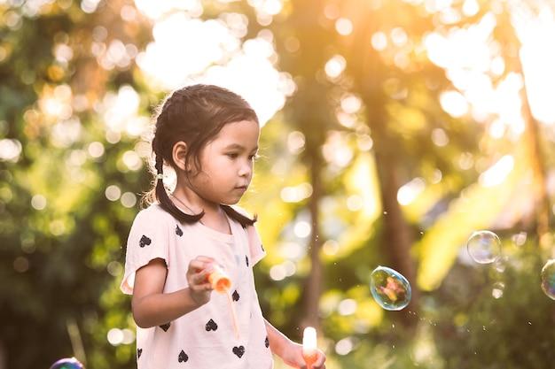 Menina asiática bonito, menina, se divertindo para brincar com bolhas ao ar livre ao pôr do sol