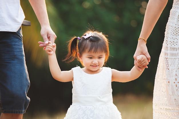 Menina asiática bonito que guarda a mão e que anda com seus pais no parque