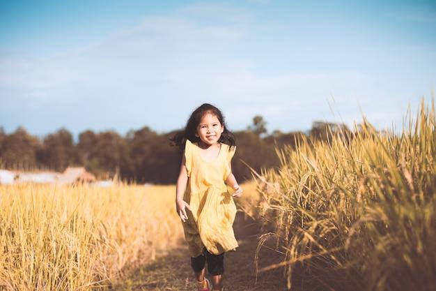 Menina asiática bonito que se diverte para correr no campo de milho no tom de cor vintage