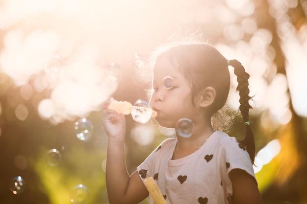 Menina asiática bonito que se diverte para soprar bolhas de sabão ao ar livre ao pôr do sol