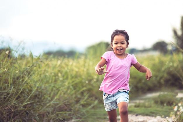 Menina asiática bonito se divertindo e correndo no parque em tom de cor vintage