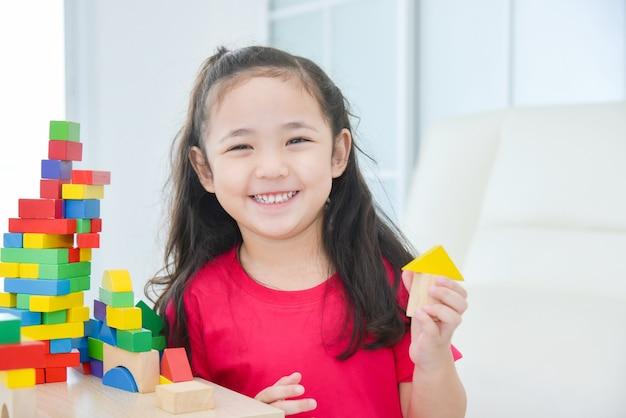 Menina asiática brincando com blocos de madeira coloridos em casa