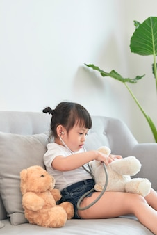 Menina asiática brincando com boneca de brinquedo