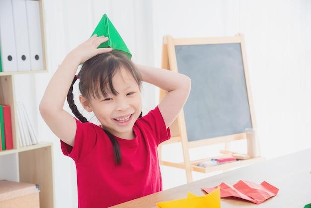 Menina asiática brincando com chapéu de papel