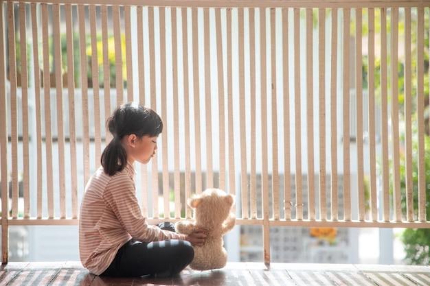 Menina asiática brincando com ursinho de pelúcia