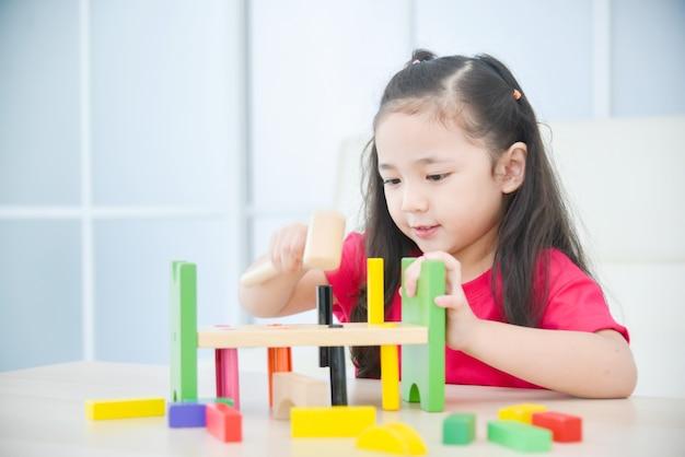 Menina asiática brincando de brinquedo em casa