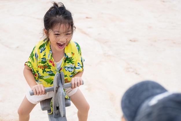 Menina asiática brincando de cadeira de balanço nas férias na praia