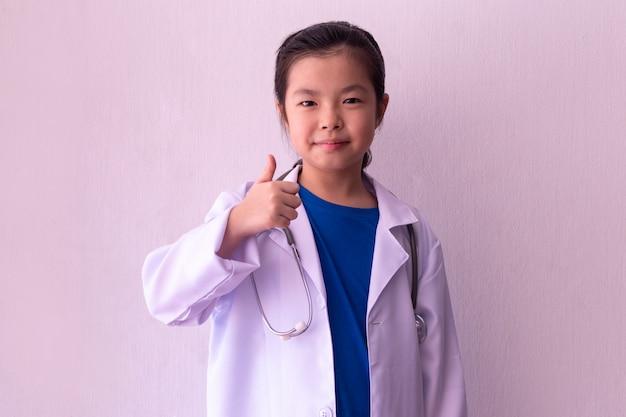 Menina asiática brincando de médico com estetoscópio nas mãos