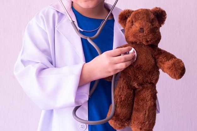 Menina asiática brincando de médico e ouvindo ursinho com estetoscópio