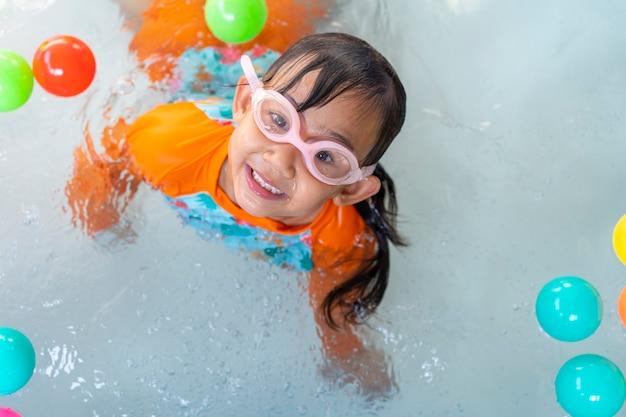 Menina asiática brincando na piscina