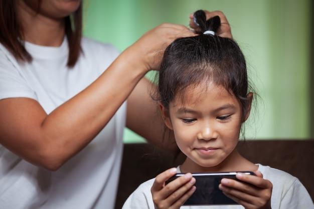 Menina asiática brincando no telefone enquanto a mãe está fazendo um penteado