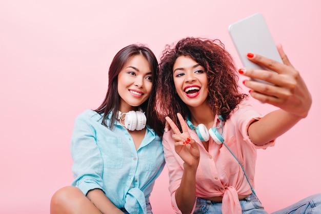Menina asiática bronzeada satisfeita, sorrindo suavemente enquanto sua amiga africana fazendo selfie. retrato interior de mulher negra feliz com smartphone tirando foto de si mesma perto da senhora hispânica.