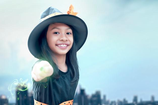Menina asiática bruxa usando a varinha com um brilho mágico
