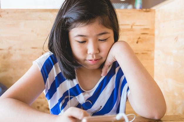 Menina asiática cabelo preto segurando jogando smartphone ouvir música