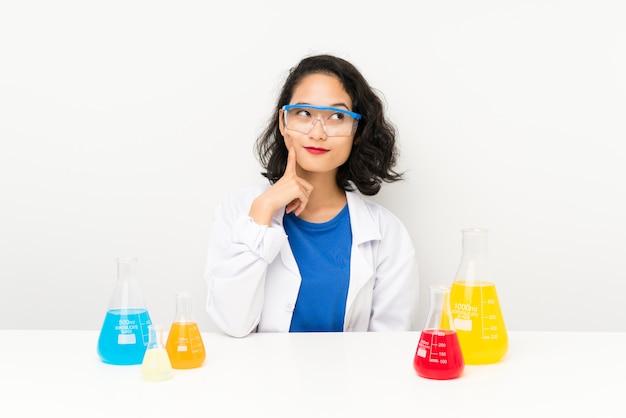 Menina asiática científica nova que pensa uma ideia