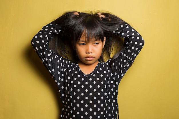 Menina asiática coçando e coçando a cabeça
