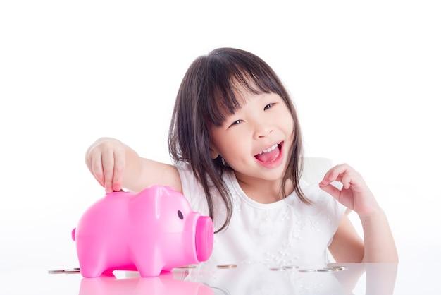 Menina asiática colocando moedas no cofrinho rosa sobre fundo branco