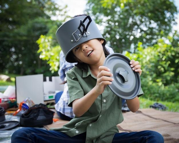 Menina asiática colocando uma tampa de panela na cabeça e se divertindo para ajudar os pais a cozinhar