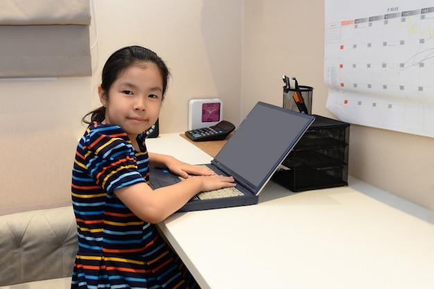 Menina asiática com computador portátil. conceito de educação.