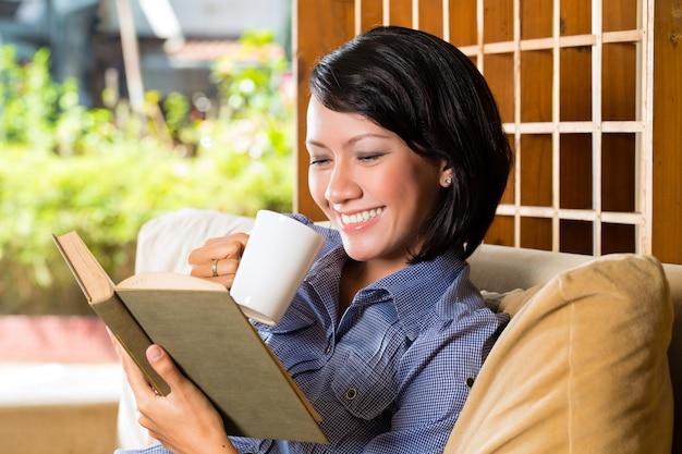 Menina asiática com copo lendo livro