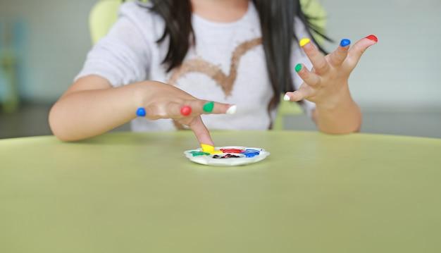 Menina asiática com dedos coloridos pintados na sala de crianças