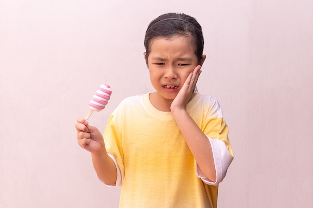 Menina asiática com dentes hipersensíveis comendo comendo um picolé congelado colorido no verão
