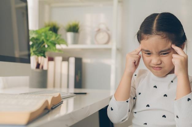 Menina asiática com dor de cabeça de fazer lição de casa