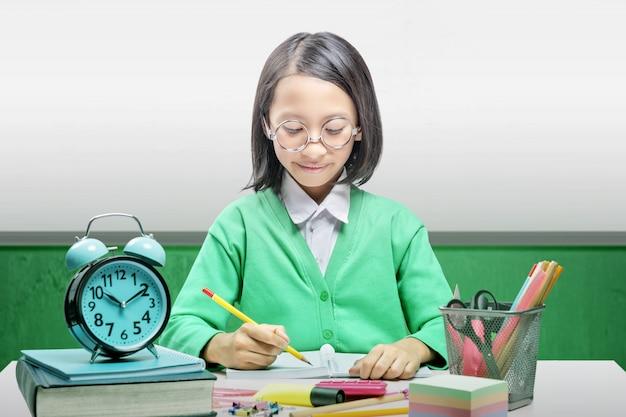 Menina asiática com estacionário escreve no livro sobre a mesa