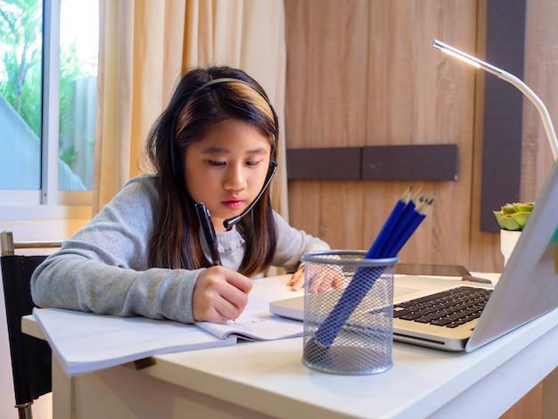 Menina asiática com fones de ouvido sentada na mesa, estudo on-line no laptop criança usando fone de ouvido, escrita à mão no caderno