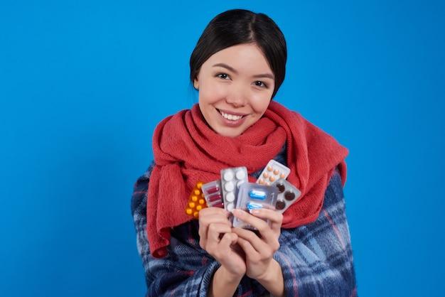 Menina asiática com frio que toma muitos comprimidos isolados.