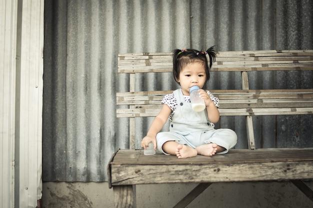 Menina asiática com garrafa de leite sentado sozinho na mesa