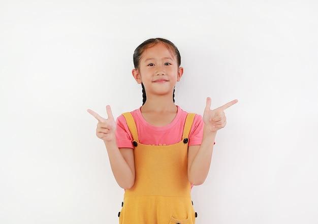 Menina asiática com gestos de dedo apontando ao lado contra um fundo branco