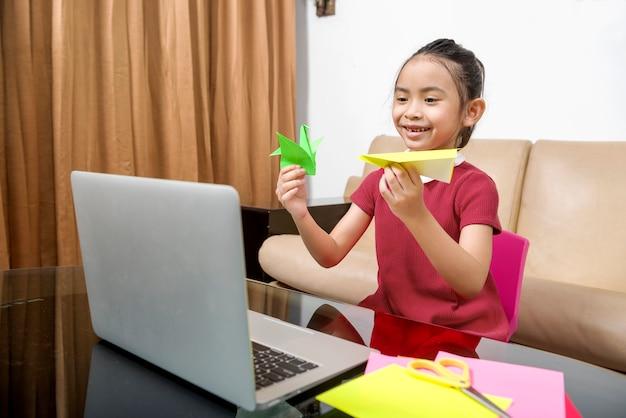Menina asiática com laptop, participando de aulas da escola online em casa. educação online durante a quarentena