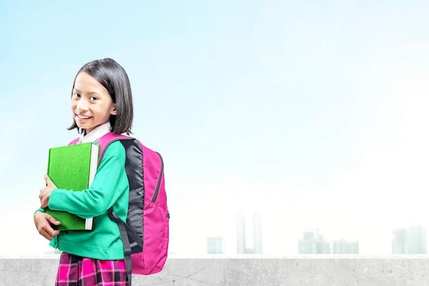 Menina asiática com livro e mochila indo para a escola