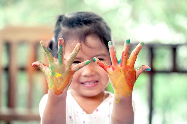Menina asiática com mãos pintadas