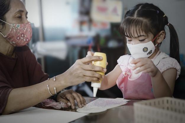 Menina asiática com máscara higiênica facial e mãe fazendo trabalho de arte juntos em casa, foco seletivo. quarentena, isolamento domiciliar durante a pandemia de covid-19.