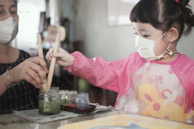 Menina asiática com máscara higiênica facial e mãe pintando aquarelas juntas em casa, foco seletivo. quarentena, auto-isolamento durante a pandemia de covid-19.