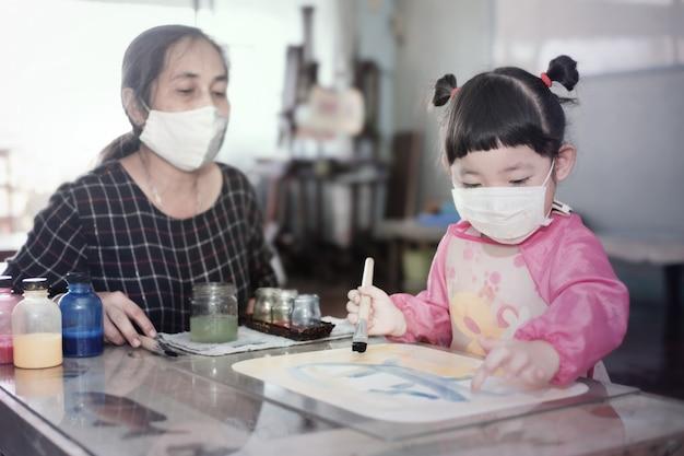 Menina asiática com máscara higiênica facial e mãe pintando aquarelas juntas em casa, foco seletivo. quarentena, isolamento domiciliar durante a pandemia de covid-19.