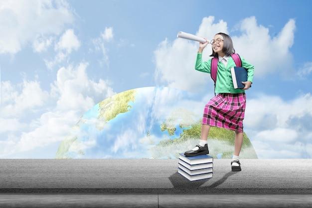 Menina asiática com mochila e binóculos com um céu azul
