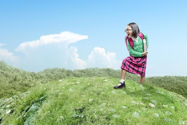 Menina asiática com mochila e livro em pé com um céu azul