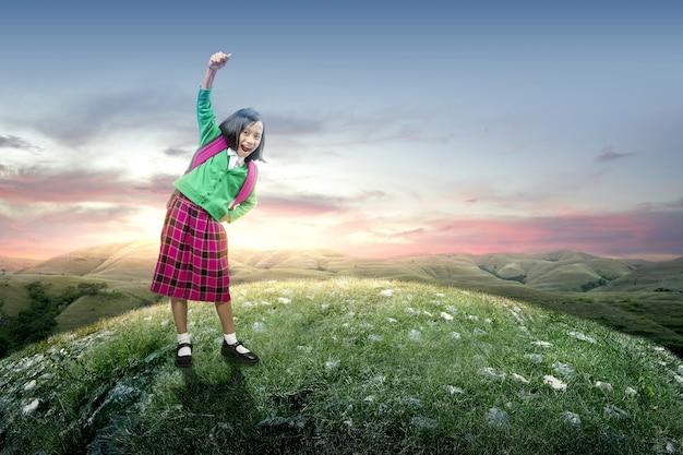 Menina asiática com mochila em pé com um céu ao pôr do sol