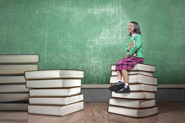 Menina asiática com óculos, sentado na pilha de livros