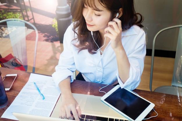 Menina asiática com os olhos fechados desfrutar de ouvir música com um laptop e fones de ouvido e relaxante