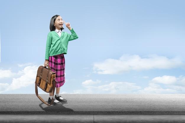 Menina asiática com pasta em pé com um céu azul